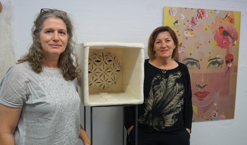 Lilian van den Einden (l) en Giny Jans naast hun kunstwerken.