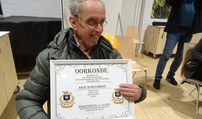 Vol trots poseert Arie Schuurman met de oorkonde van het erelidmaatschap die hem zojuist door de voorzitter is uitgereikt.
