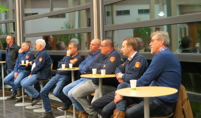 Brandweerlieden op de publieke tribune luisteren mee naar de antwoorden van de burgemeester op vragen over een redvoertuig.