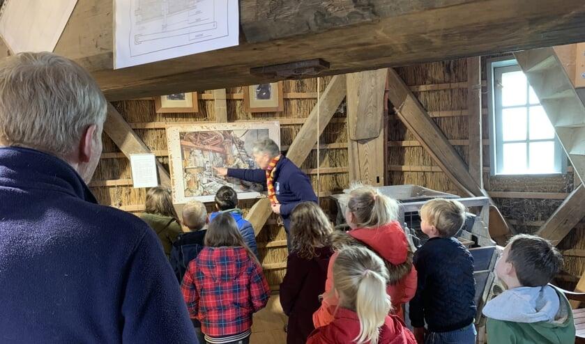 Kinderen volgen binnen aandachtig de uitleg via een oude plaat.