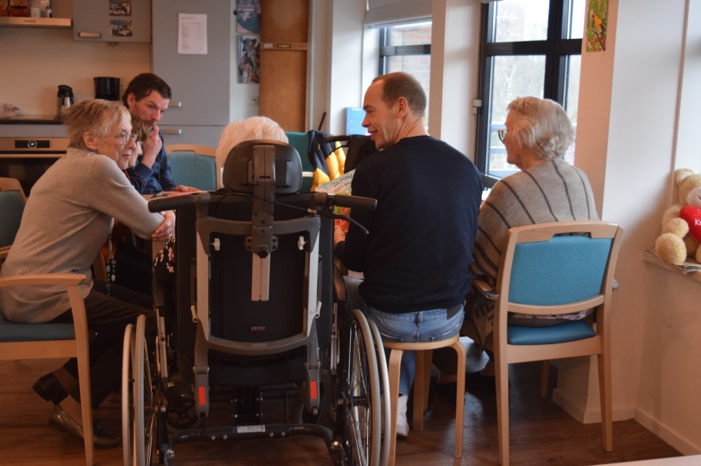 Twee leerkrachten van De Nijepoort lezen de ouderen voor.  © De Vierklank
