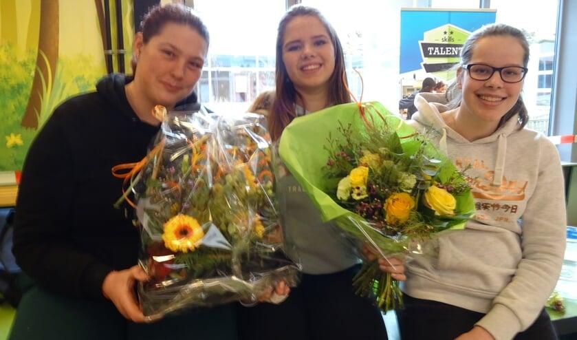 Fenna, Tess en Simone tonen trots het door hen gemaakte bloemwerk.