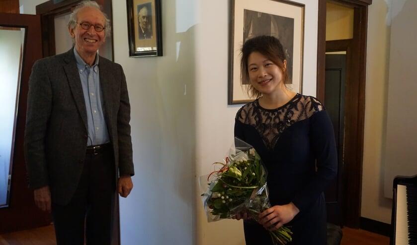 Vivianne Cheng met de zojuist van voorzitter Hans Zwarts ontvangen bloemen.
