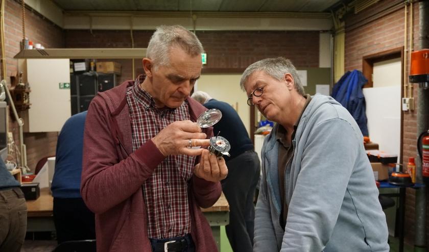 Vrijwilliger Aart onderwerpt het defecte klokje van een oldtimer aan een nauwkeurig onderzoek.