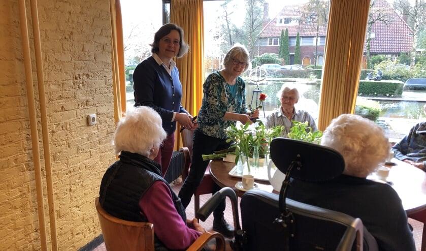 Martine Pol (staand links) van Lionsclub Utrecht Kromme Rijn overhandigde 11 maart het bedrag aan Marlies Dijkkamp (rechts) van Wooncentrum Schutmantel en zette de eerste bloemen op tafel.