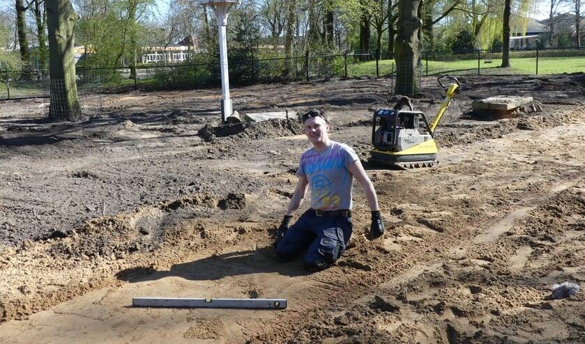 Vrijwilliger Ruud Copijn druk in de weer met de aanleg van het looppad op de omgespitte dierenweide .