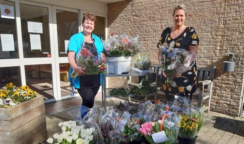 Nicolien Ahaidour en Lia Bicker, zorgmedewerkers van de Bremhorst, nemen 50 bossen bloemen in ontvangst.