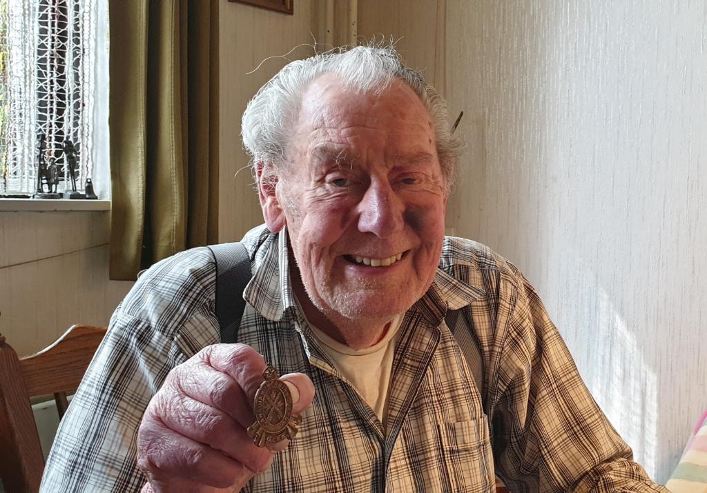 Bart Kuus met het jarenlang bewaarde baretembleem. Foto:  © De Vierklank