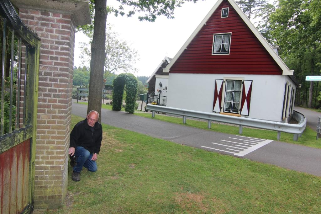 Henk Kuus wijst op het ingangshek de plek aan de stenen hoekpaal af brak. Op de achtergrond zijn geboortehuis Het Tolhuis. Foto: Henk van de Bunt © De Vierklank