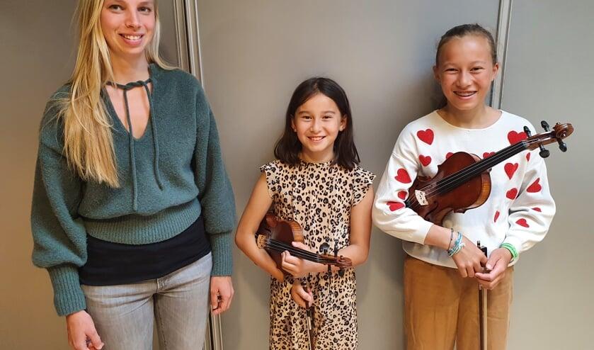 Zangcoach Lea Zantinge (l) met haar pupil Amelie (m) en zusje Amber (r).