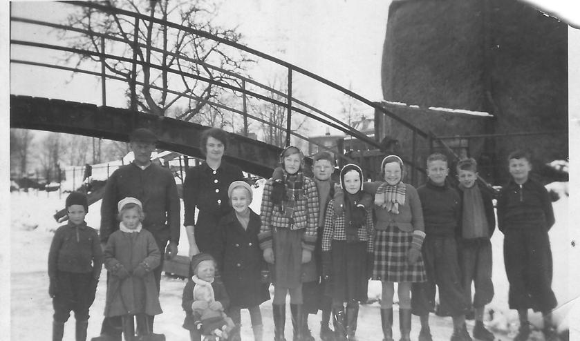 Eef(je) zittend op de slee met haar zus (links), vader en moeder en overige buurtkinderen op het ijs van De Grift bij de een aantal jaren geleden afgebroken brug ter hoogte van de benzinestations.