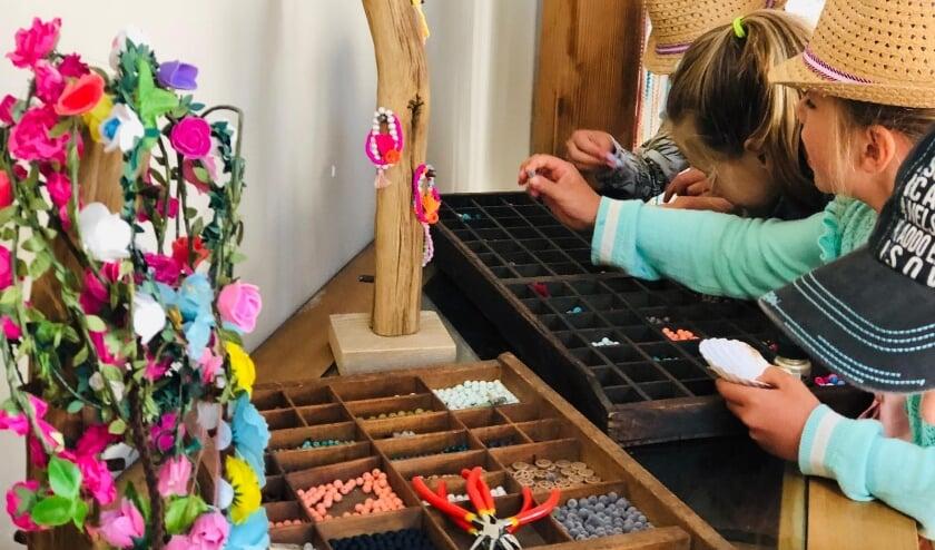 Kinderen kiezen materialen voor Ibiza armbandjes. (foto Hip and Happy events)