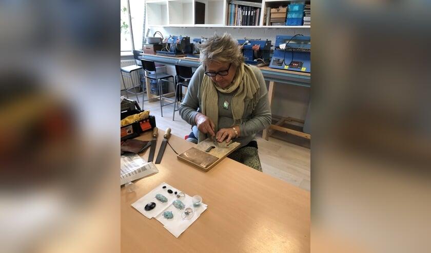 Marga Langenkamp is bezig een zelfgemaakte zilveren ring te vijlen zodat deze mooi glad wordt.
