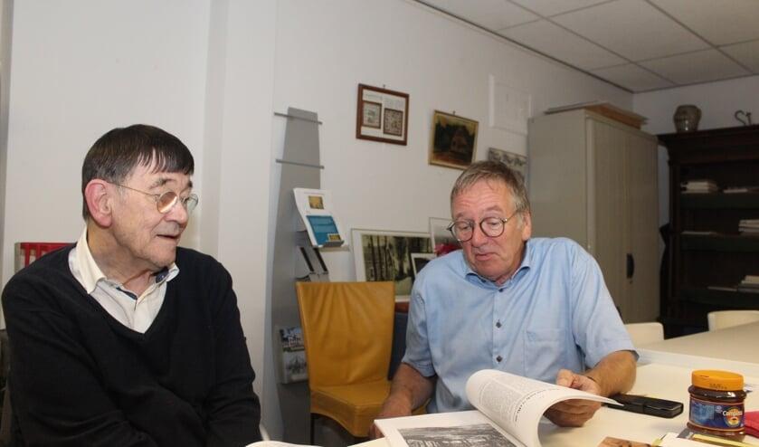 Koos Kolenbrander en Jan Maasen bladeren door de analoge verzameling van de Maartensdijkse dorpschroniqueur.