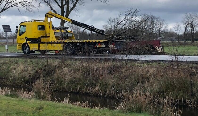 De brandweer heeft de boom die over de auto lag, afgezaagd waarna de berger de auto kon afvoeren. (foto Marcel Röhrs)