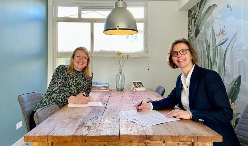 Fleur Imming (links) en Saskia Knoop (rechts) tekenen het sponsorcontract