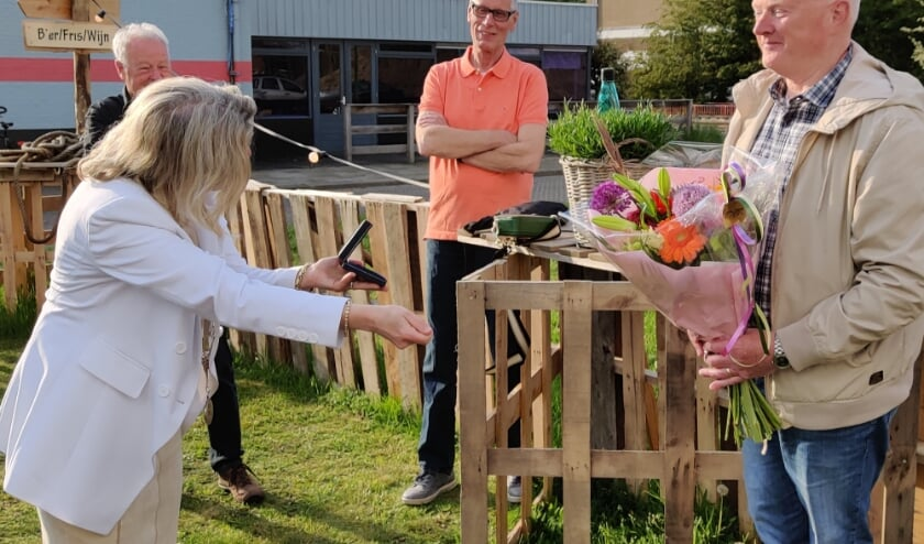 Na de bloemen overhandigt de locoburgemeester met een diepe buiging de chapeau-penning aan Ron Smit.