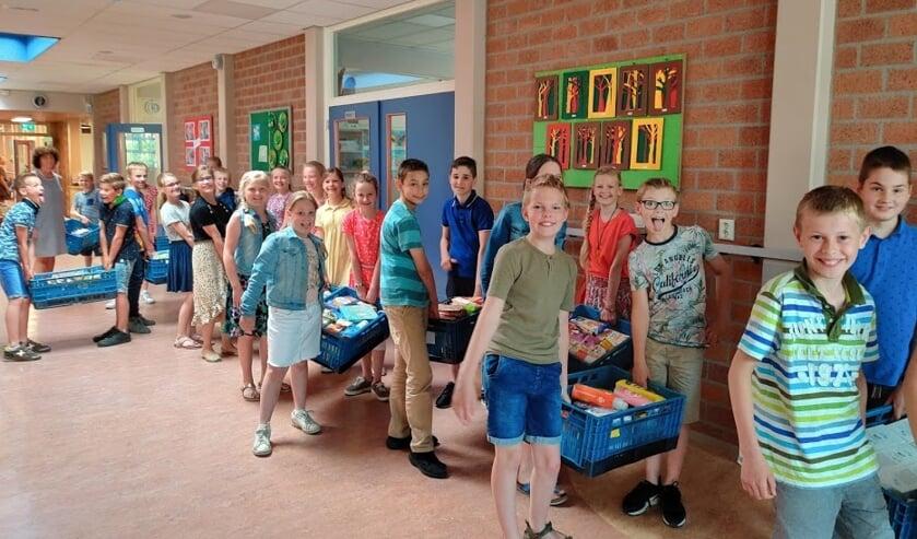 De leerlingen ielpen graag met het sjouwen van de gevulde kratten.