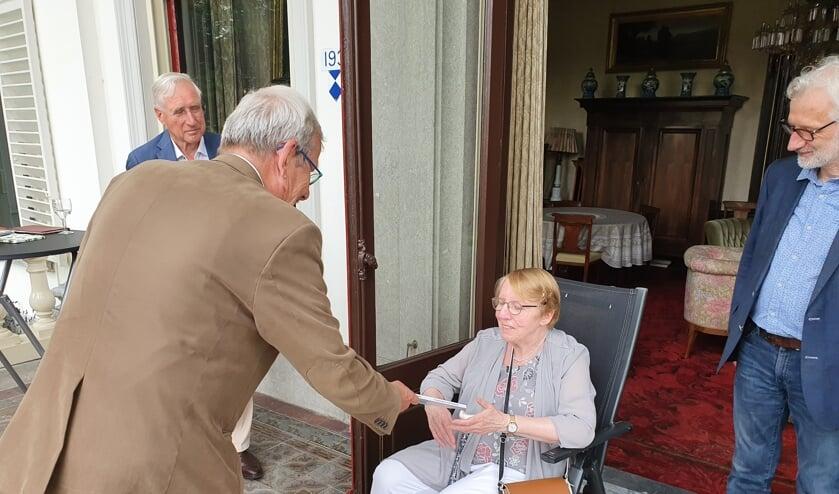 Onder toeziend oog van (links) Arie-Jan Ditewig (Online Museum) en (rechts) Otto van Boetzelaer overhandigt Anne Doedens het eerste boek aan Serieke Verschuur, partner van de in april overleden coauteur Pieter van Hees.