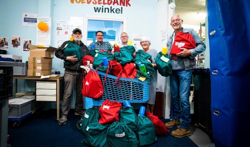 Vertegenwoordigers van de deelnemende kerken leveren de tasjes af bij De Voedselbank. (foto Jeroen Jumelet)