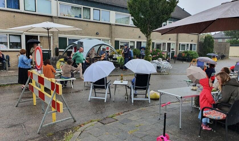 Ondanks de vele regen kwamen omwonenden met eten, drinken en paraplu's om te luisteren naar nummers van de A.S. Streetband.