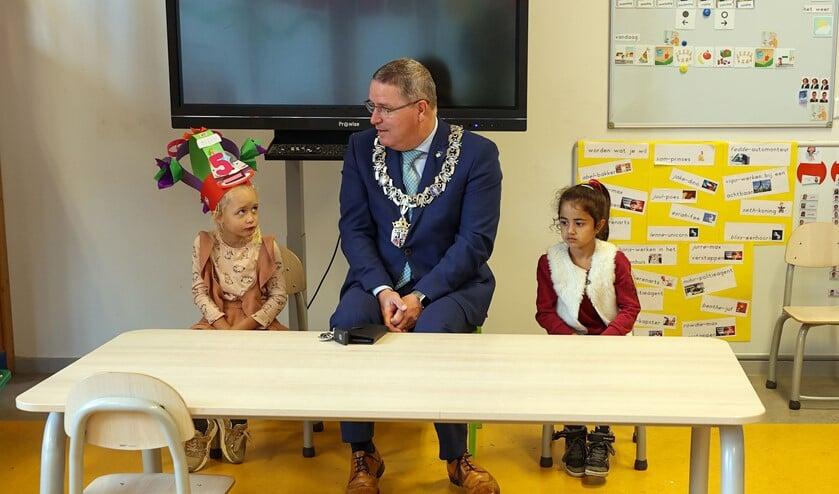 Burgemeester Marcel Delhez met Bliss en Esrah uit groep 1/2A. FOTO: Bert Jansen.