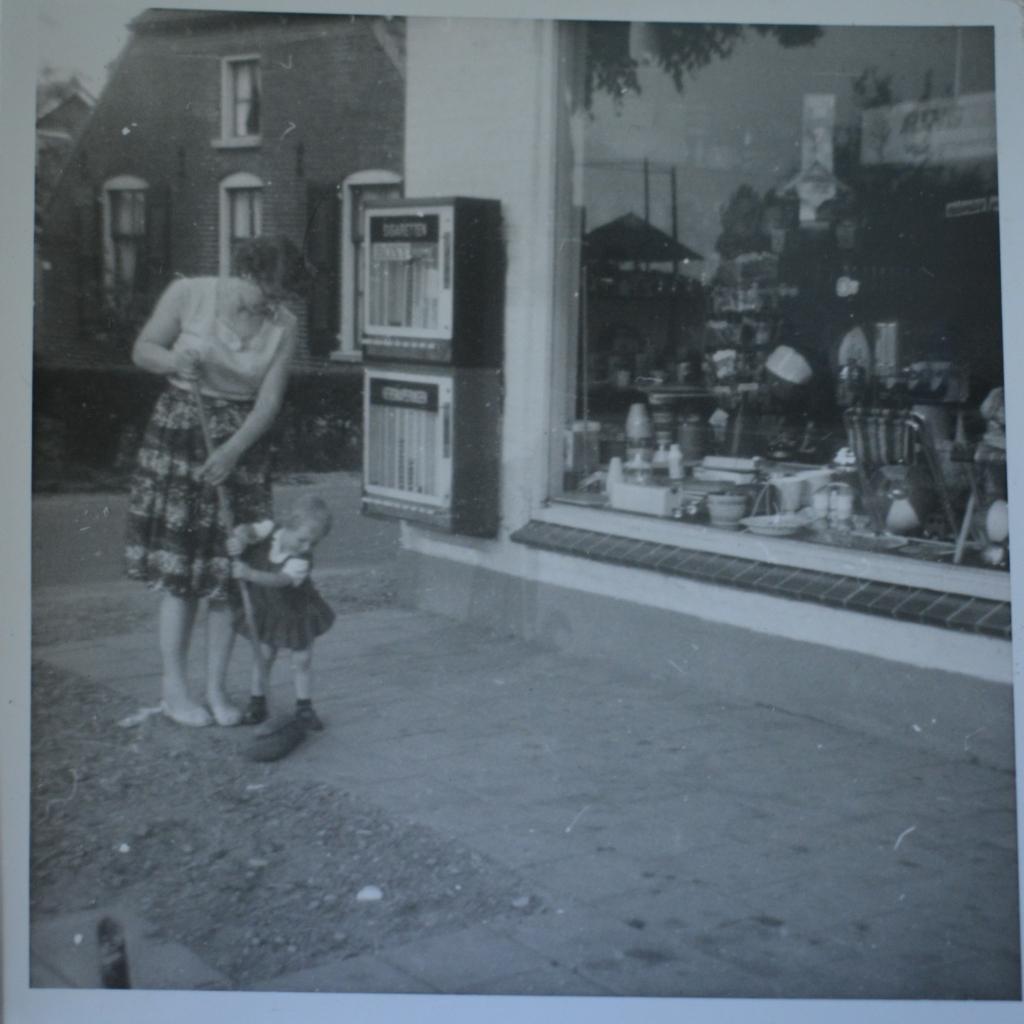 Een piepjonge Zwiertje helpt haar moeder de stoep voor de winkel vegen.  © De Veluwe Koerier