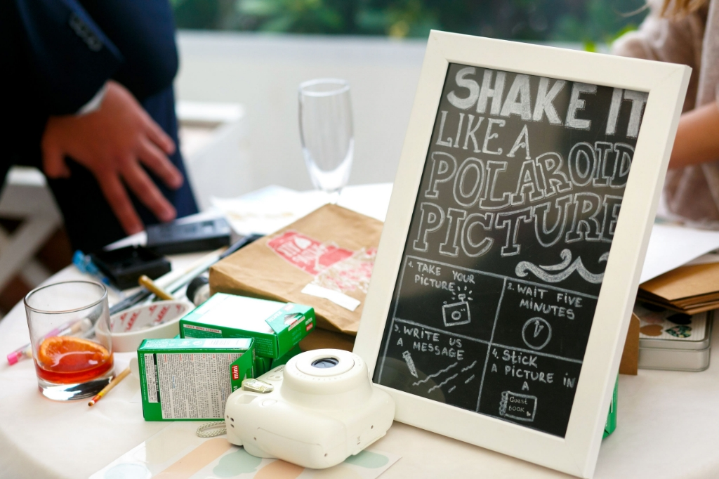 Black board with a lettering about polaroid stands on the table Foto:  © Alblasserwaard