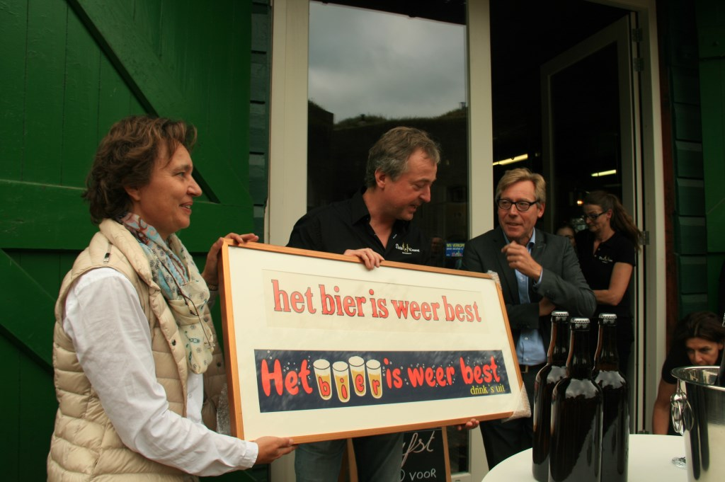 • Daniëlle Duits en Marco Lauret ontvingen uit handen van Cees-Jan Adema een antiek reclamebord.  Foto: Dick Aanen © Vianen