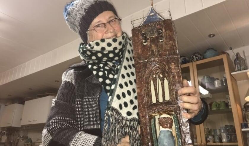 Keramiste Jeannette Huizenga-Luteijn levert een kunstzinnige bijdrage aan de actie om het angelusklokje weer in oude glorie te herstellen. Zij maakte een goed gelijkende miniatuur van de scheve St. Janstoren. (Foto: Janneke Severs-Hilgeman)