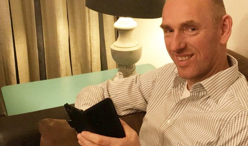 • Jan Holtslag aan het twitteren op zijn mobiel.