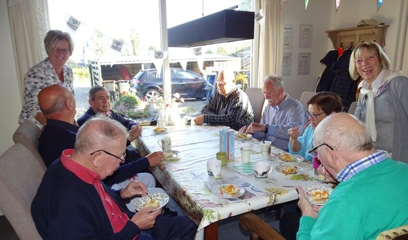 • Begeleiders Anja, Henk en vrijwilligster Jeanette genieten samen met de ouderen van een feestelijke traktatie.