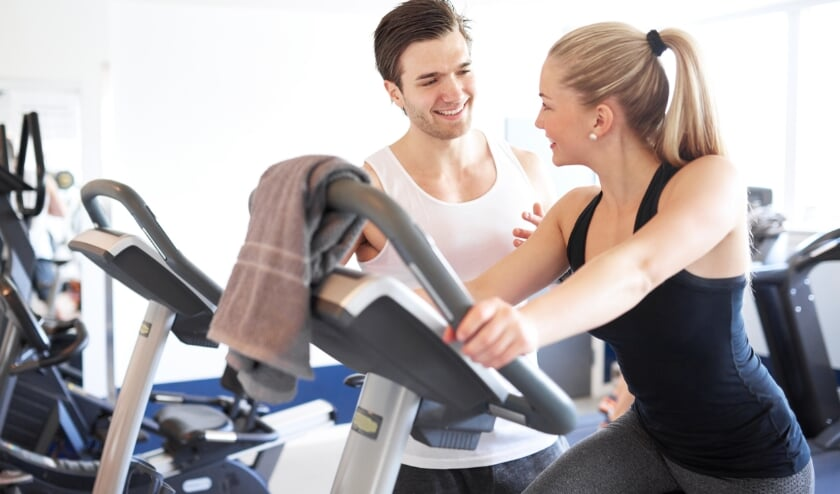 <p>Handsome Young Fitness Trainer Explaining Something to a Young Woman While on Elliptical Bike Device Inside the Gym</p>
