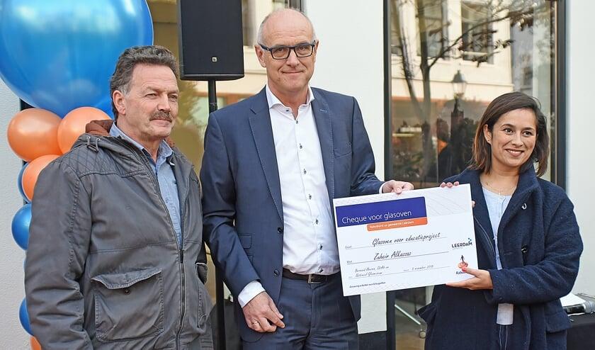 • Teus Meijdam en Martijn Spijk overhandigen de cheque aan Sacha Kraan.