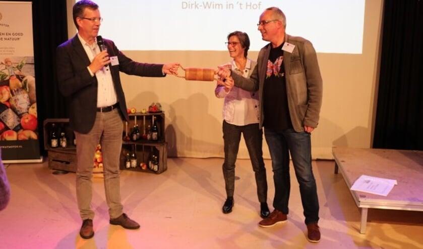 Joost Reus overhandigt het circulaire estafettestokje aan Hilde Engels en Henri Holster van De Fruitmotor