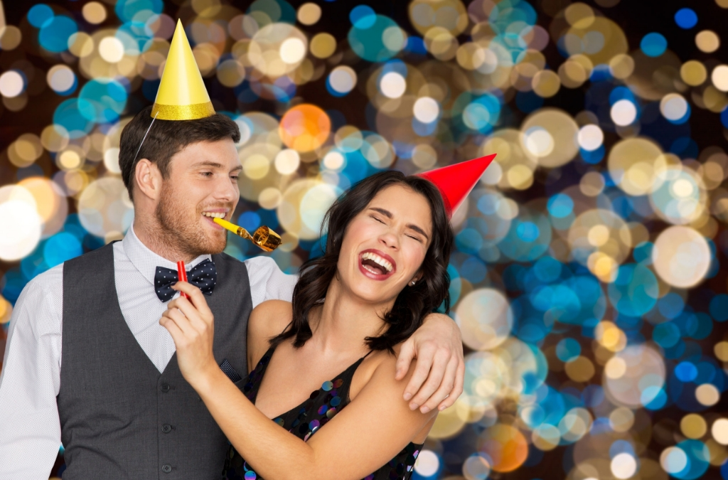 birthday, celebration and holidays concept - happy couple with party blowers and caps having fun over festive lights background Foto: lev dolgachov © Alblasserwaard