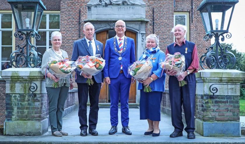 • De vier gedecoreerden samen met burgemeester Harry de Vries.