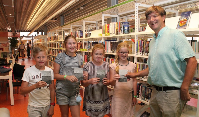 • Koos van Dam, Debora Jongeneel, Dieudonnée Verloop en Marjolein Buitelaar (v.l.n.r.) overhandigen de gedichtenbundels aan Bart van Aanholt van de bibliotheek.