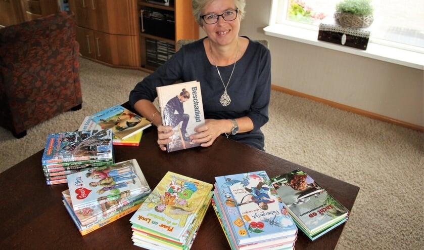 • Teunie Suijker met al haar boeken. In haar hand haar nieuwste boek: Beschadigd.