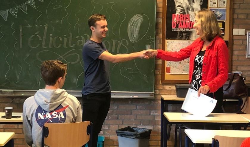 • Docent Hermien Hol overhandigt een DELF-diploma aan een leerling.
