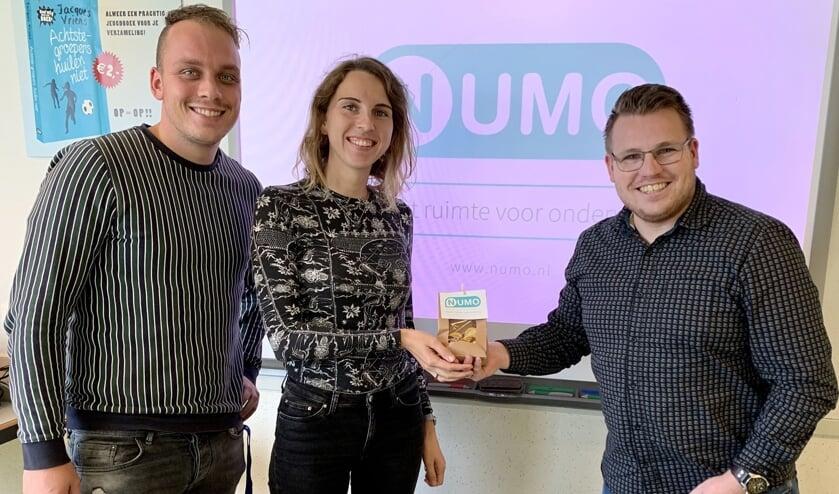 • Docenten Sigrid van Tuijl en Danny van Dijk ontvangen chocolade-Numo's uit handen van Numo-expert Nico Wagter (r).
