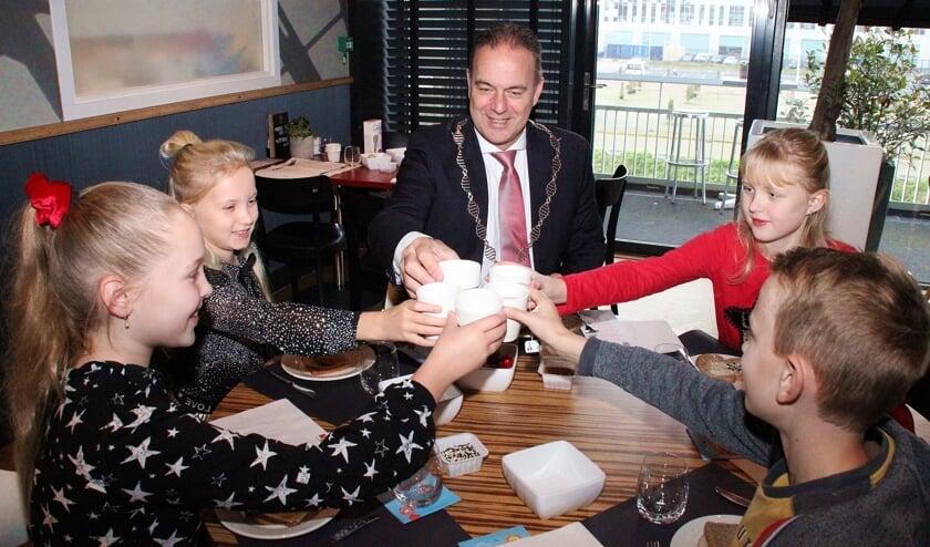 • De kinderen toasten met de burgemeester op het lekkere ontbijt.