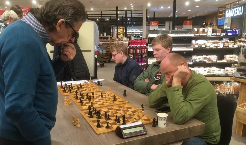 • Wim van Oostrum geeft simultaan aan een drietal borden tegelijkertijd.