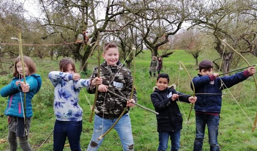 Kinderen schieten met hun eigengemaakte pijl en boog.