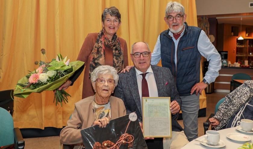 • Lie van Riessen-van Leeuwen samen met burgemeester Henny van Kooten. Daarachter staan de zoon en dochter van Lie.