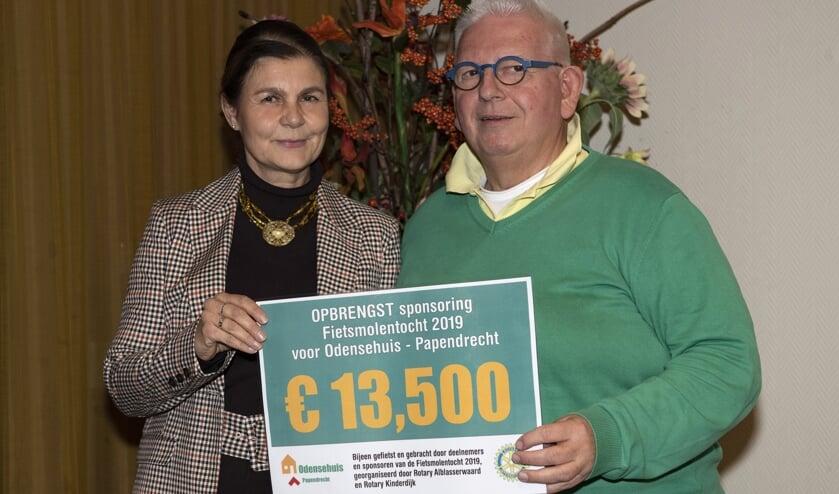 • : Jacqueline van den Bergen overhandigt de cheque aan Piet Bezemer in bijzijn van betrokkenen van Odensehuis en Rotary.