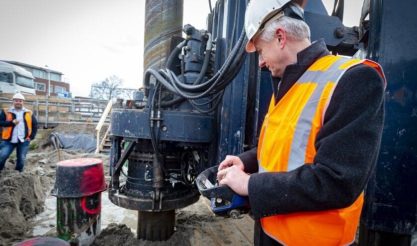 • Projectwethouder Anthon Timm bedient de knoppen en drukt zo de eerste funderingspaal de grond in.