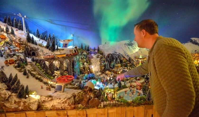 Mark van Kippersluis legt in de woonkamer de laatste hand aan zijn 5 meter lange, maar zeer sfeervolle kerstdorp. (Foto: Paul van den Dungen)
