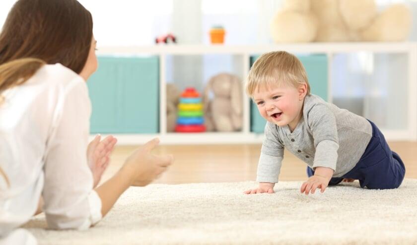 • Een pedagogisch medewerker met een kruipend kind.