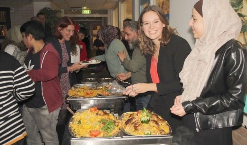 Marlieke van Schalkwijk kreeg bij het serveren van het diner spontaan hulp van Rayan, een van de gasten. (Foto: Lysette Verwegen)
